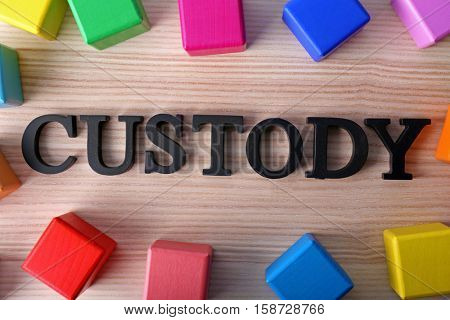 Word CUSTODY and cubes on wooden background, top view