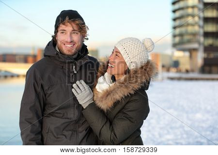 Winter couple in snow hat and coats. Happy young adults walking together smiling on a city street enjoying sunny urban walk in modern neighborhood. Asian girlfriend in love with man.