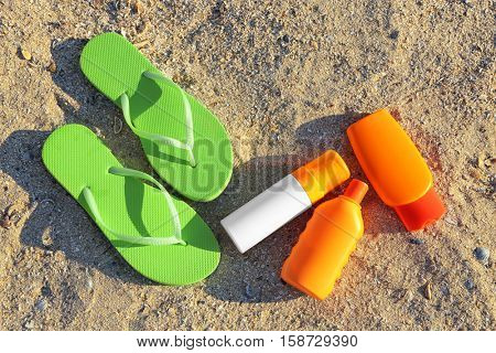 Green sandals and sunscreen cream on sea sand