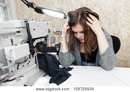Tailor with strong headache at sewing machine, free space. Seamstress having attack of migraines at workplace. Troubles, healthcare, disease concept