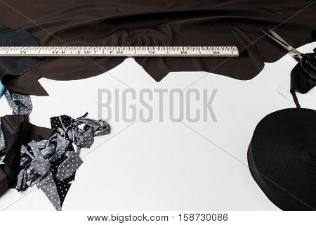 Tailor designer workplace flat lay, free space. Top view on white table with dark fabric and measuring tape, copy space on white background. Fashion, garment industry, clothes making atelier concept