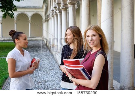 Three young females friends all together at college campus