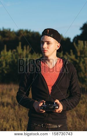 Young man standing with rc transmitter outdoor. Attractive guy attentively looking for piloting drone. Hobby, leisure, entertainment, innovations, electronics, technology concept