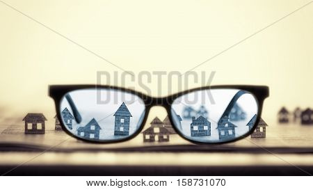 Eyeglasses lie on the open newspaper with paper houses. That could mean rent search purchase real estate.