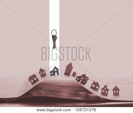 Image of a open newspaper with paper houses on red background. Above one house stands bunch of keys. House and keys are marked in white.
