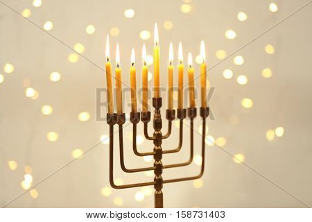 Menorah with candles for Hanukkah against defocused lights