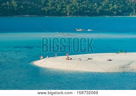 Beautiful long shot of sand dune white sandy beach and blue calm sea with people enjoy sun bathing and other activities on the beach with the small boat, Phuket, Thailand