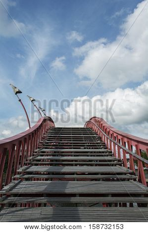 Wooden stairway with red banister in the blue sky with clouds