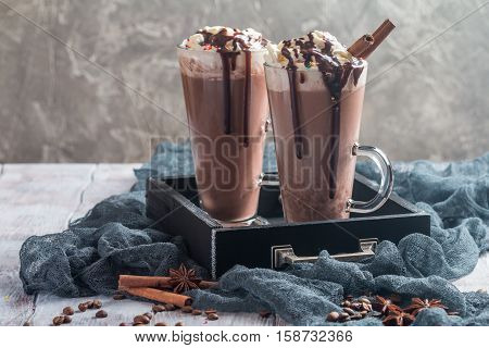 Ice chocolate in tall glass mugs with whipped cream and chocolate sauce on table