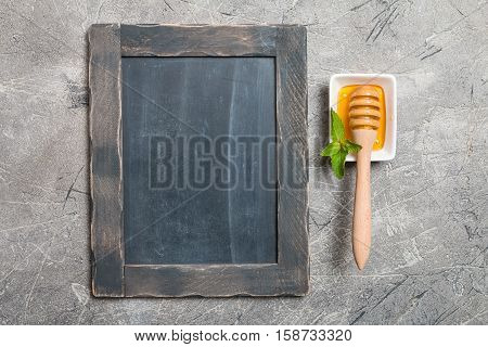 Organic Honey with Honey Dipper in a white bowl on gray slate background, top view with copy space