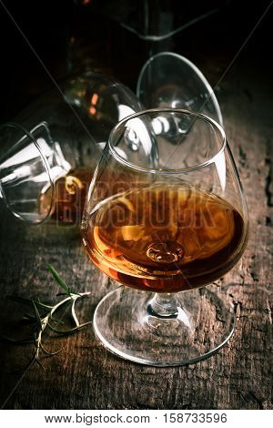 Glass of brandy or cognac on old oak wooden table. Dark photo.