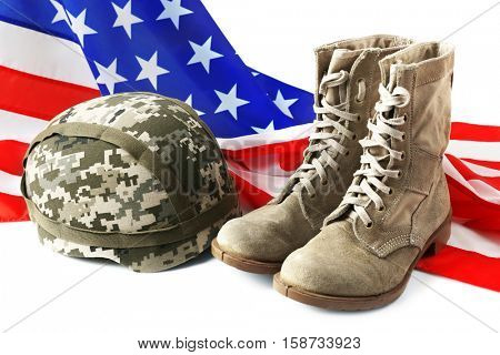 Pair of combat boots, military helmet and USA flag on white background