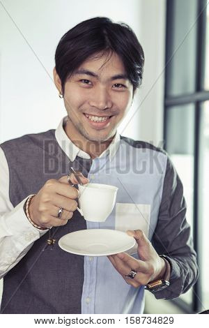 asian younger man toothy smiling face with hot coffee cup in hand