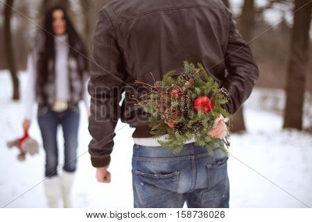 Young man holding winter bouquet behind his back dating girlfriend and celebrating valentines day. Young couple in love outdoor. Outdoor christmas portrait of young stylish fashion couple posing in park. Snowing winter