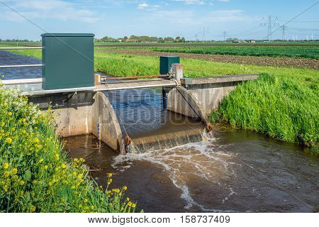 Closeup of a small weir in a stream for water level control in a Dutch polder with high voltage lines and pylons in the background.