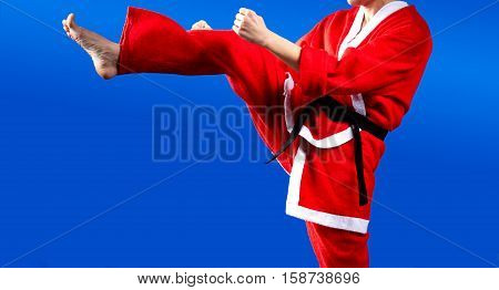 On a blue background beats karateka kicking in a suit of Santa Claus