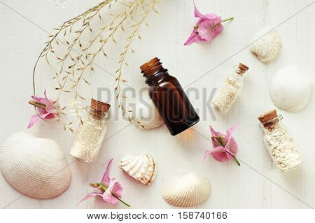 Essential oil, bottles with sand, sea shells, tropical flowers, top view white wooden spa treatment background. Relaxation set.
