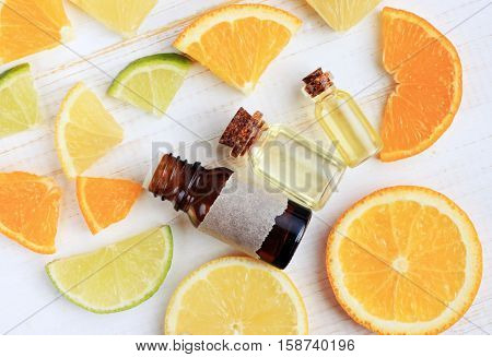 Array of Citrus scents. Natural aromatherapy. Fresh bright slices mix of different fruit, essential oil in glass bottles, top view, wooden table. Empty craft label.