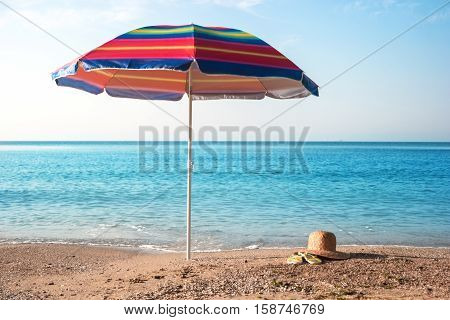 Umbrella on beach. Sky and seashore. Far from bustle and noise. Good place to relax.