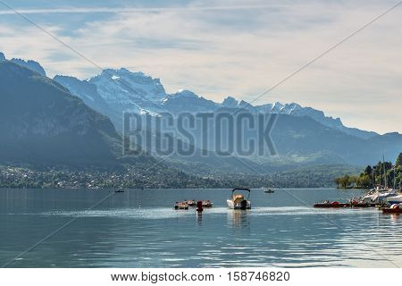 Beautiful view of the Annecy Lake in French Alps a spring day with snow in the mountains and with boats in the foreground. Annecy Haute Savoie French Alps France.