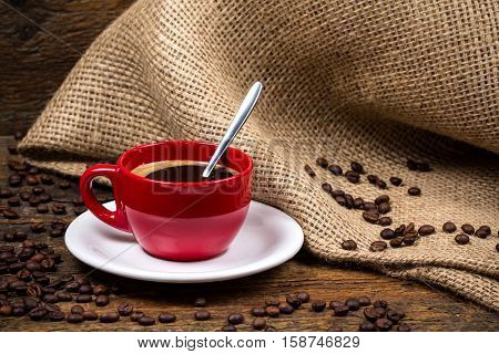 Coffee cup with metallic spoon and surrounding coffeebeans and gunny textile