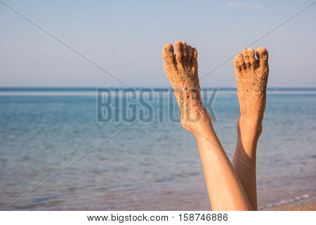Female legs on sea background. Feet covered in sand. No bustle and problems. Vacation of your dreams.