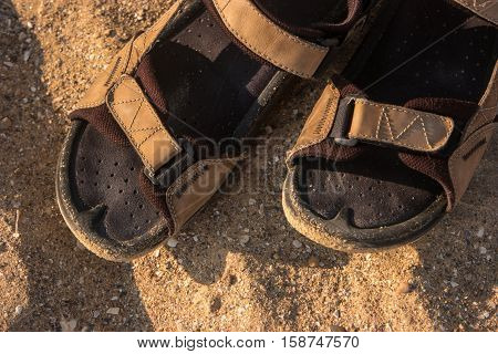 Pair of sandals on sand. Men's summer footwear. Hot summer in the tropics. Explore and wander.