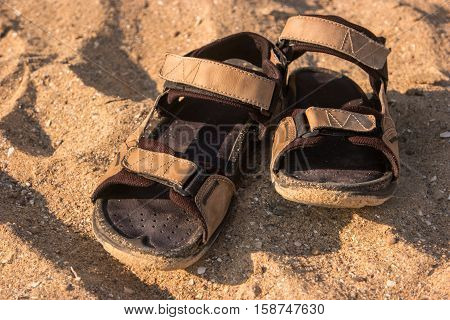 Sandals on the sand. Men's light footwear. Summer in the tropics. Wander and explore island.