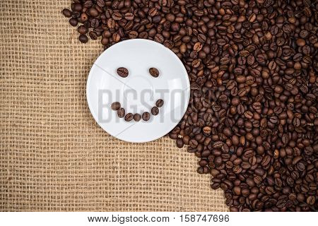 White coffeeplate with smiley coffeebeans on gunny background