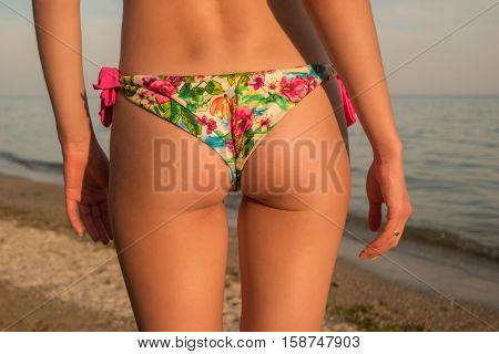 Butt on background of sea. Young woman's body. Warmth and beauty. Fit for summer.