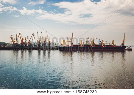 Pier and cranes. Side view of freight ship. Maintenance and repairs. Unload the cargo.