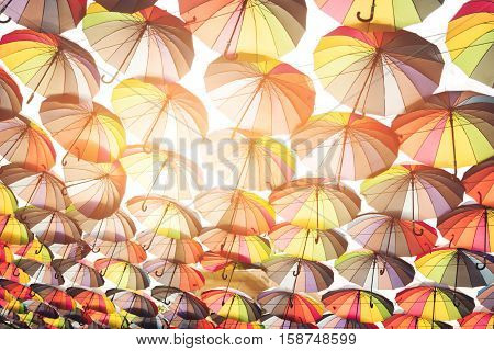Lots of multi colored umbrellas. Umbrellas and sunlight. Bright palette of joy. Colors that cheer you up.