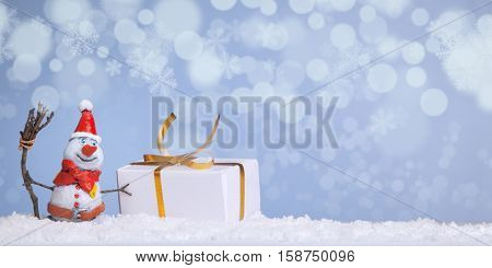 Christmas snowman in the snow with giftbox against the backdrop of snowflakes and illumination