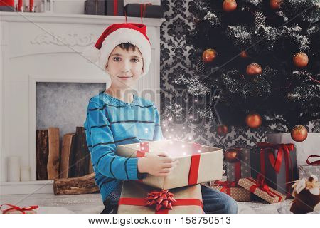 Christmas miracle. Cute happy boy in santa hat unwrap magic present on holiday morning in beautiful room. Male child open Xmas gift near decorated fir tree and fireplace. Winter holidays concept