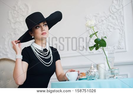 Woman in hat, much like the famous actress, croissant eating and drinking tea