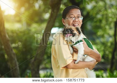 Cheerful Singaporean man standing with dog in his hands