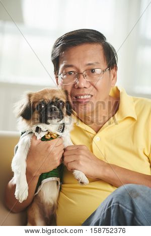 Portrait of smiling Singaporean man with little dog looking at camera