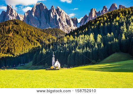 Dolomites, Tirol. Sunny autumn day. The famous symbol of the valley Val di Funes - church of Santa Maddalena. Rocky peaks and forested mountains surrounded by green Alpine meadows