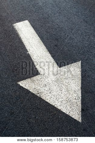 White arrow on asphalt road traffic sign marking on roadway