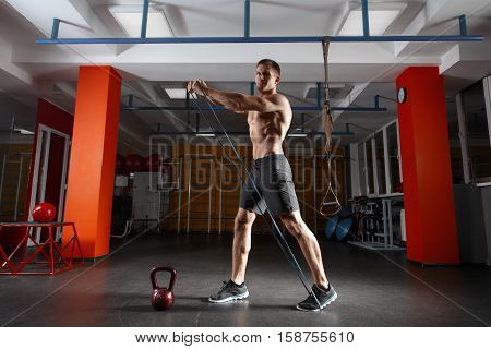 Fitness man exercising with stretching band in the gym. Muscular sports man exercising with elastic rubber band. Guy working out with rubber band. Fit, fitness, exercise, workout and healthy lifestyle