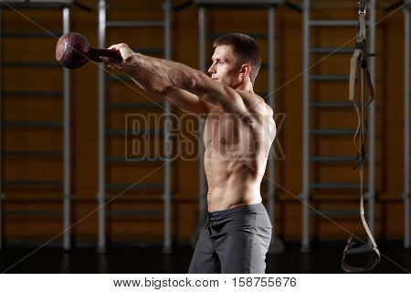Fitness man doing a weight training by lifting kettlebell. Young athlete doing kettlebell swings. Bodybuilder lifting kettlebell