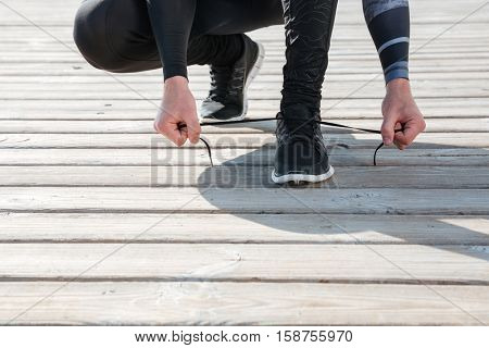 Cropped image of runner preparing near the sea. tying shoelaces