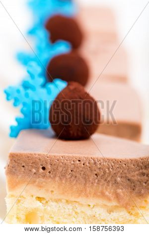 Delicious mousse cakes with chocolate truffles and blue mastic snowflakes. Macro. Photo can be used as a whole background.
