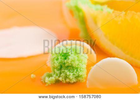 Kiwi siphon sponge on orange glazed cake. Macro. Photo can be used as a whole background.