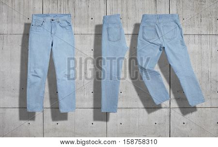 Classic light blue womens jeans shot as a set from the front, back and folded in half on industrial concrete background