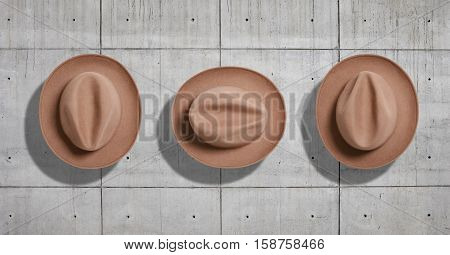 Classic felt beige fedora hat shot from the top in three different rotations as a set isolated neutral gray concrete industrial background