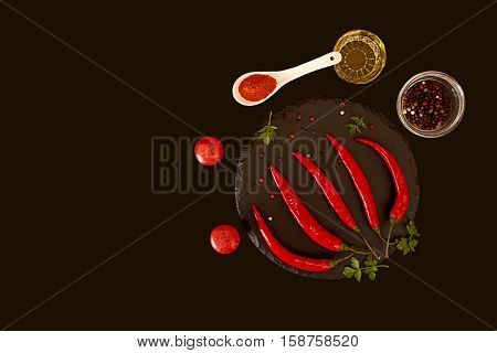 Red chili pepper on stone slate on black background. Composition of group burning spicy chili peppers ground pepper oil bowl and red and black bell pepper. Top view. Copy space