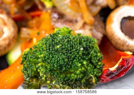 Closeup of delicious baked broccoli as a garnish for pork shish kebab. Macro.