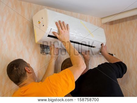 Voronezh, Russia - December 25, 2015: Two workers install the air conditioner in the apartment