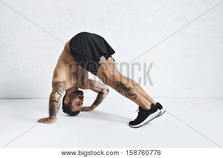 Strong brutal tattoed and ripped male athlete shows how to do pike push-ups, isolated on white spacious room, low position